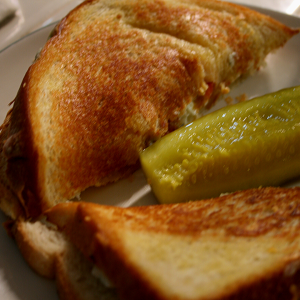 Bleu Monday Grilled Cheese served with a kosher dill pickle.