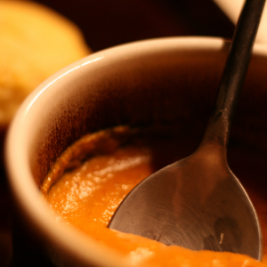 A cup of Creamy Curried Pumpkin Soup served with a corn muffin.